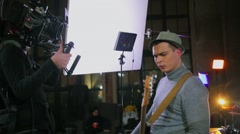 Operator shots guitarist in hat with professional camera equipment in studio Stock Footage
