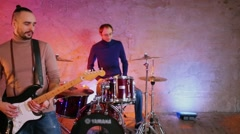 Guitarist and drummer performs in studio with illuminated wall Stock Footage