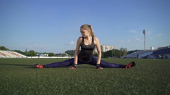 Young female athlete doing stretching and sits on twine Stock Footage