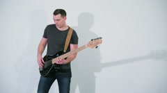 Musician plays on guitar at studio with white background Stock Footage