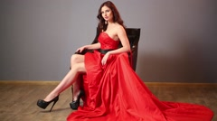 A woman in a long red dress and high heels in the chair Stock Footage