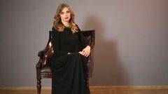 Beautiful young woman in a long black dress sitting in a chair Stock Footage