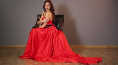 Beautiful woman in a long red dress sitting in a chair Stock Footage