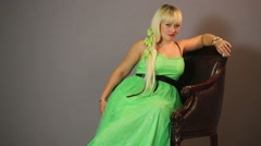 Beautiful blonde woman in a long green dress sitting in a chair Stock Footage