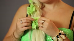 Hands of woman straightens her hair with artificial green flowers Stock Footage