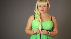 Beautiful woman in a bright green dress corrects hair and turns Stock Footage