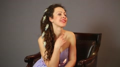A smiling woman in a purple dress sitting in a chair Stock Footage