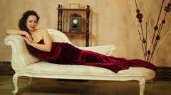 Woman in maroon dress lies on white sofa near the shelf with clock Stock Footage