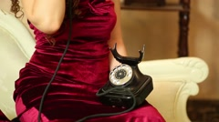 Woman in maroon dress holding the old phone handset to the ear Stock Footage