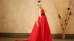 Woman corrects a long red dress and looking into the camera Stock Footage