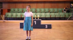 Girl bows and begins to dance at competition in dance school Stock Footage