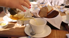 Female hand pours from a glass kettle black tea in a cafe outdoors Stock Footage