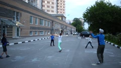 Five children playing frisbee in the yard of an apartment house Stock Footage