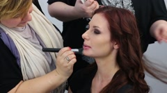 Professional make-up artist and hair stylist working with girl Stock Footage