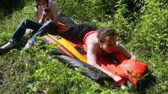 Woman with her daughter is deflated rubber boat on the grass Stock Footage