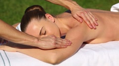 The masseur kneads the shoulders of a young woman outdoors Stock Footage