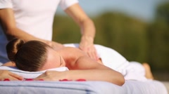Young woman enjoying a relaxing massage in the open air Stock Footage