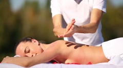 Masseur rub oil in his hands and doing massage for a young woman Stock Footage