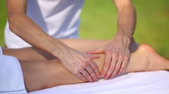 Masseur massaging the leg of a young woman outdoors Stock Footage