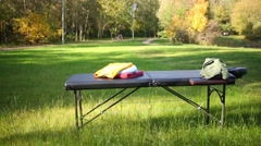 Massage table with a pile of towels in a sunny autumn park Stock Footage