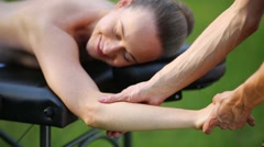 The masseur kneads woman hand on a massage table in the park Stock Footage