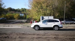 Cars and people cross the broken road covered with earth and gravel Stock Footage