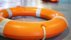 Orange lifebuoy lying on the floor next to the pool Stock Footage