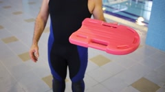 Man in wetsuit holding a swimming board in the pool Stock Footage