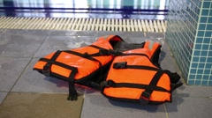 Orange life jacket lies on the edge of an indoor swimming pool Stock Footage