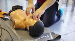Man fulfills first aid skills on a mannequin in the Training Center Stock Footage