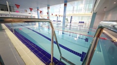 Stairs in the indoor swimming pool with lanes and flags Stock Footage