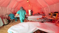 Patients in beds and doctors in tent during special tactical teachings Stock Footage