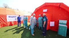 Doctors in uniform standing at entrance to tent in mobile hospital Stock Footage