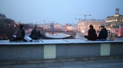 People sit on the bridge over drainage channel and look at the city Stock Footage