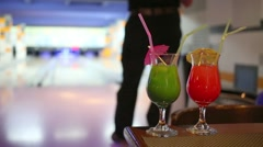 Two cocktail on a table on the background of man playing bowling Stock Footage