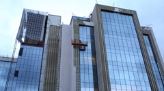 Two workers in a cradle carry out facing of modern office building Stock Footage