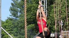 A short hair woman climing up a rope Stock Footage