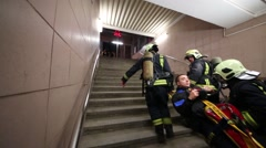Rescue workers carry up the stairs a man depicting victim on stretches Stock Footage