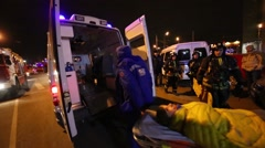 Doctors carry victim in disaster lying on a gurney in an ambulance Stock Footage