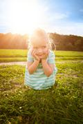 Adorable blond little girl with cheeky smile, outdoors play time - stock photo