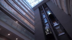 The Interior of Modern Architecture Threw Glass the Elevator Rises Stock Footage