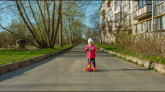 Cute little toddler girl riding scooter in the city, kids sport. autumn, in coat Stock Footage