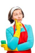 Beautiful pensive woman with a sponge thinks that to clean, isolated Stock Photos