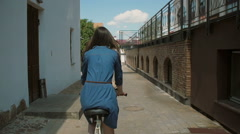 Back view of a girl in a dress riding a bike with flowers in basket Stock Footage