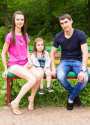 Young family mom dad daughter sitting on a bench in summer Park Stock Photos