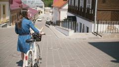 Girl wearing sunglasses walking her bike down the street Stock Footage