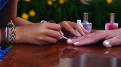 Close-up of hands of schoolgirl doing a manicure for her grandmother Stock Footage