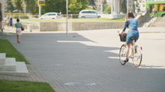 Back view of a brunette girl riding a bike near busy road with driven cars Stock Footage