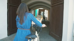 Back view of a brunette girl walking with a bike into old gate in old town Stock Footage