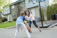 Happy family having fun outside with a basketball Stock Photos
